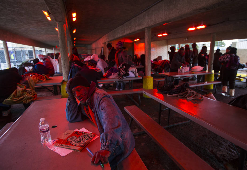 Donald Rice, left, talks about staying warm beneath a heat lamp after a night of snowfall at the city of Las Vegas' homeless courtyard on Thursday, Feb. 21, 2019. (Chase Stevens/Las Vegas Review-J ...