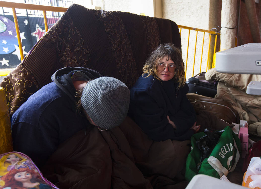Charles Peterson, left, and his fiance Edith, stay warm under a blanket after a night of snowfall at the city of Las Vegas' homeless courtyard on Thursday, Feb. 21, 2019. The couple struggled to s ...