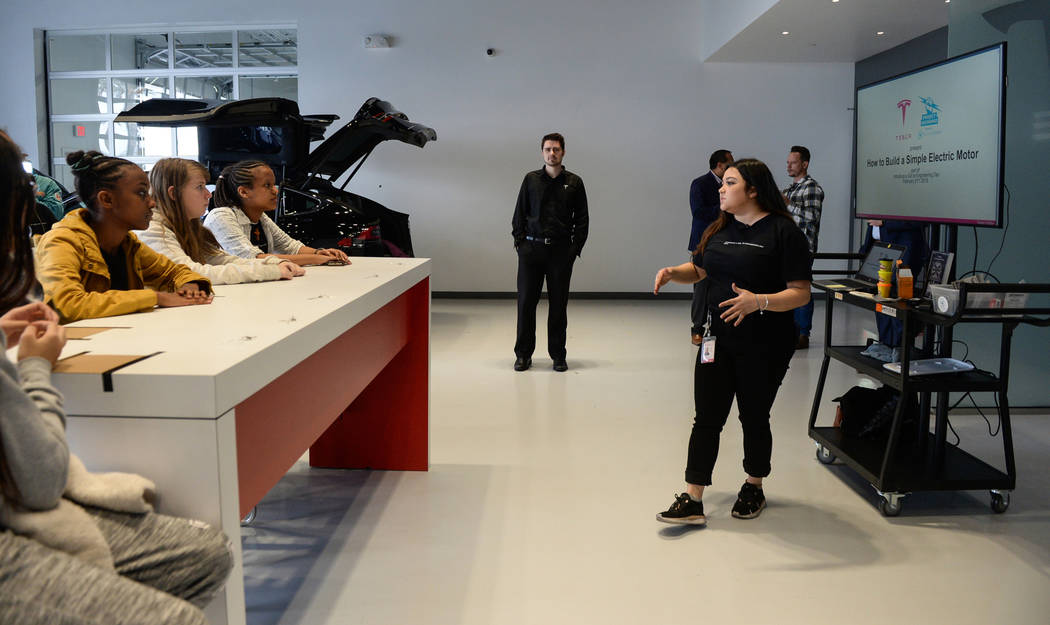 """Middle school students listen to a lesson on electric motors as Tesla celebrates """"Introduce a Girl to Engineering Day"""" at its Sahara showroom in Las Vegas, Thursday, Feb. 21, 2019. (Caroline Brehm ..."""