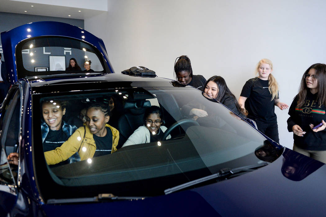 """Middle school students check out one of the Tesla cars on display as Tesla celebrates """"Introduce a Girl to Engineering Day"""" at its Sahara showroom in Las Vegas, Thursday, Feb. 21, 2019. (Caroline ..."""