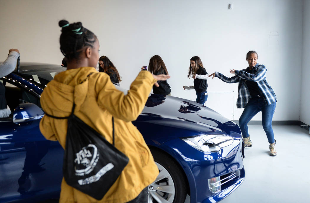 """Middle school students dance to music they put on in one of the Tesla cars on display as Tesla celebrates """"Introduce a Girl to Engineering Day"""" at its Sahara showroom in Las Vegas, Thursday, Feb. ..."""