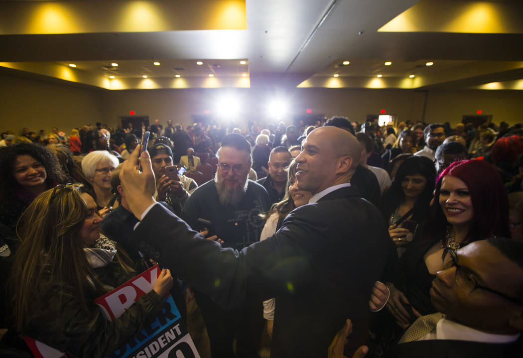 U.S. Sen. Cory Booker, D-N.J., a Democratic presidential hopeful, takes a selfie while greeting attendees during a campaign rally at the Nevada Partners Event Center in North Las Vegas on Sunday, ...