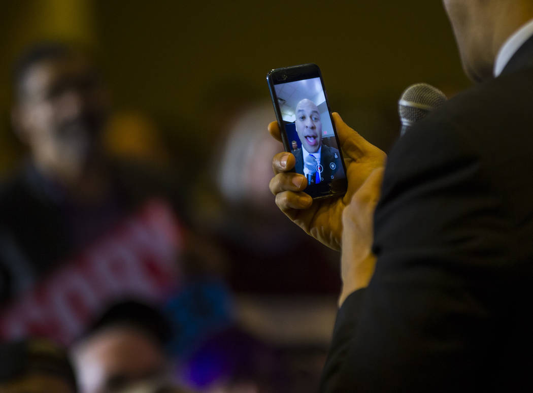 U.S. Sen. Cory Booker, D-N.J., a Democratic presidential hopeful, records a video message on the phone of an attendee during a campaign rally at the Nevada Partners Event Center in North Las Vegas ...