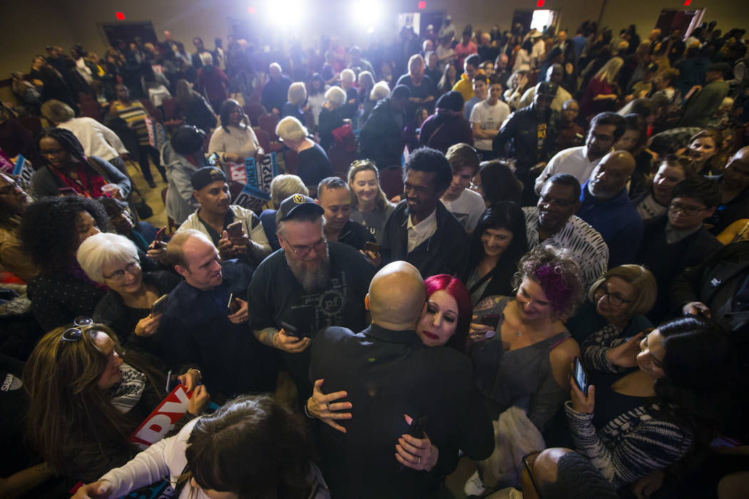U.S. Sen. Cory Booker, D-N.J., a Democratic presidential hopeful, hugs a supporter during a campaign rally at the Nevada Partners Event Center in North Las Vegas on Sunday, Feb. 24, 2019. (Chase S ...