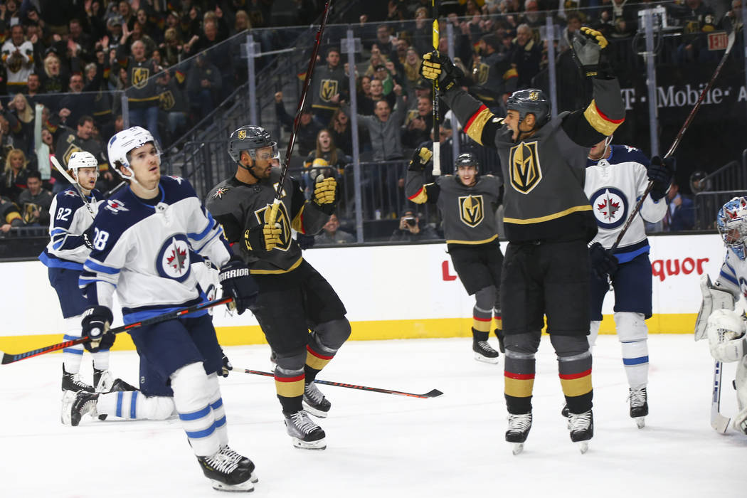 Golden Knights center Pierre-Edouard Bellemare, left, and right wing Ryan Reaves (75) celebrate a goal against the Winnipeg Jets as Jets center Jack Roslovic, left, reacts during the first period ...