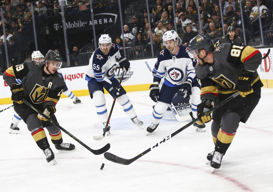 Golden Knights right wing Reilly Smith (19) and center Jonathan Marchessault (81) look to get control of the puck against Winnipeg Jets center Mark Scheifele (55) and defenseman Josh Morrissey, th ...