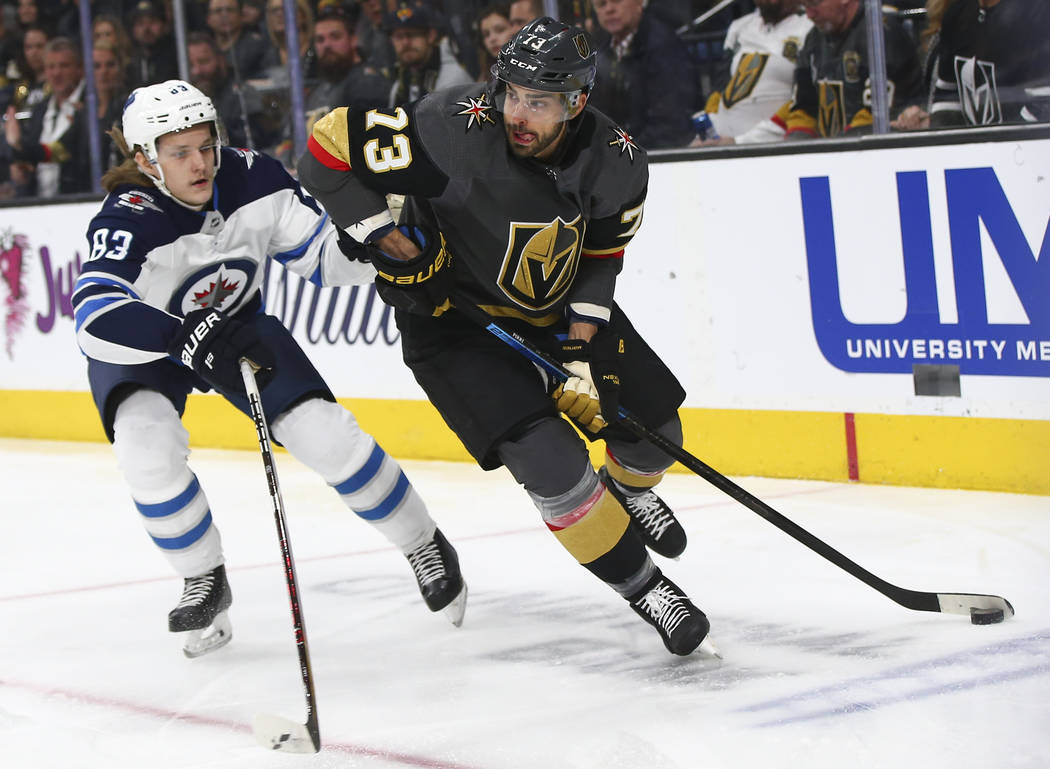 Golden Knights center Brandon Pirri (73) moves the puck around Winnipeg Jets defenseman Sami Niku (83) during the first period of an NHL hockey game at T-Mobile Arena in Las Vegas on Friday, Feb. ...