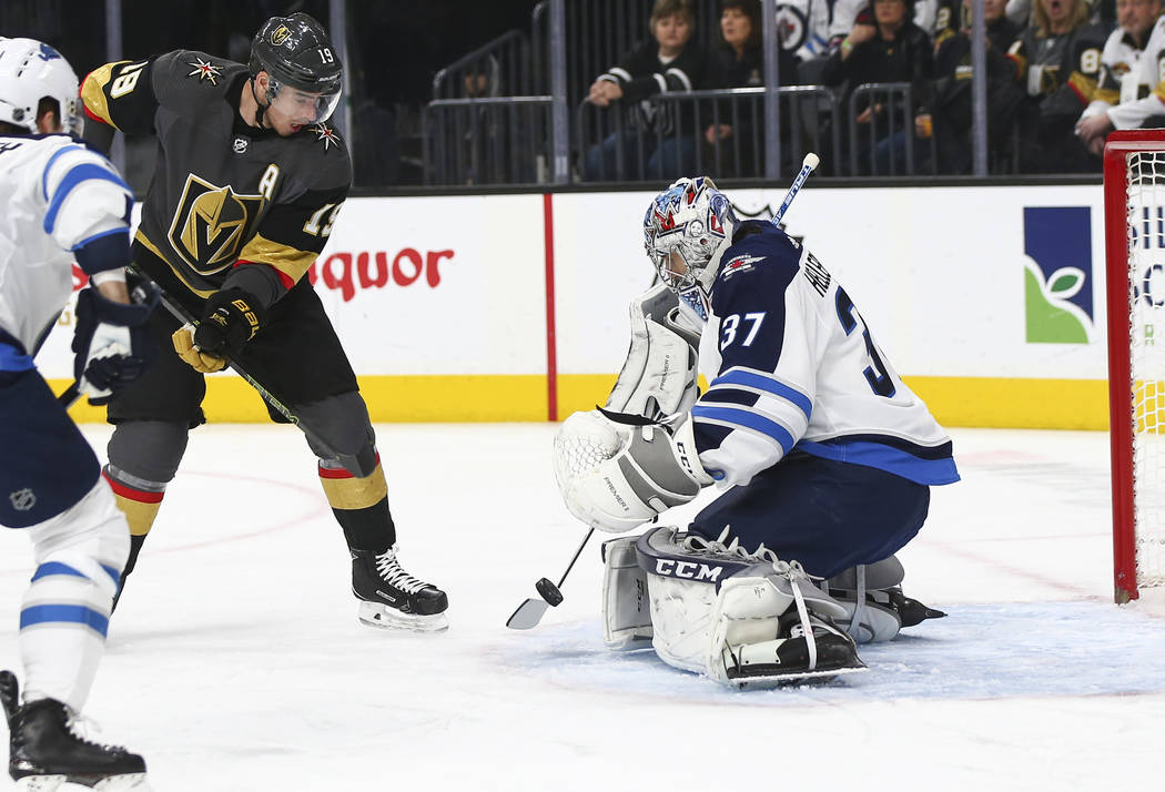 Winnipeg Jets goaltender Connor Hellebuyck (37) blocks a shot in front of Golden Knights right wing Reilly Smith (19) during the first period of an NHL hockey game at T-Mobile Arena in Las Vegas o ...
