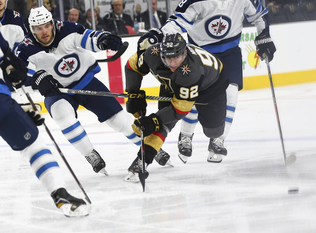 Golden Knights left wing Tomas Nosek (92) chases after the puck against Winnipeg Jets defenseman Ben Chiarot (7) during the second period of an NHL hockey game at T-Mobile Arena in Las Vegas on Fr ...