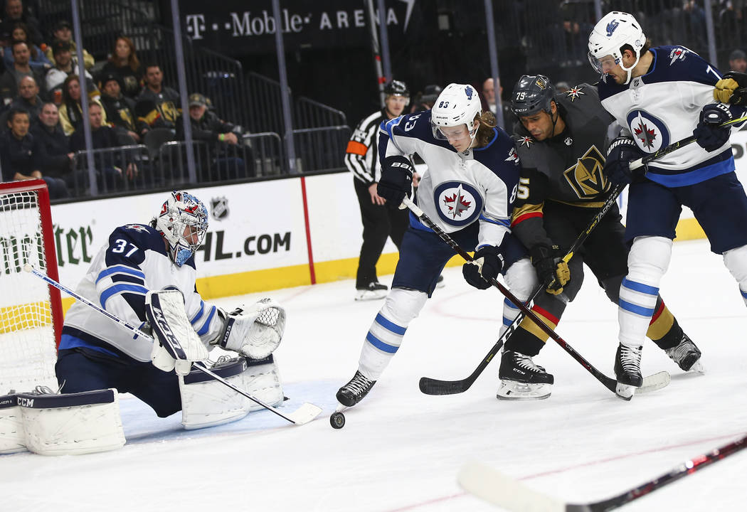 Golden Knights right wing Ryan Reaves (75) tries to get the puck in against Winnipeg Jets goaltender Connor Hellebuyck (37) and Winnipeg Jets defenseman Sami Niku (83) during the second period of ...