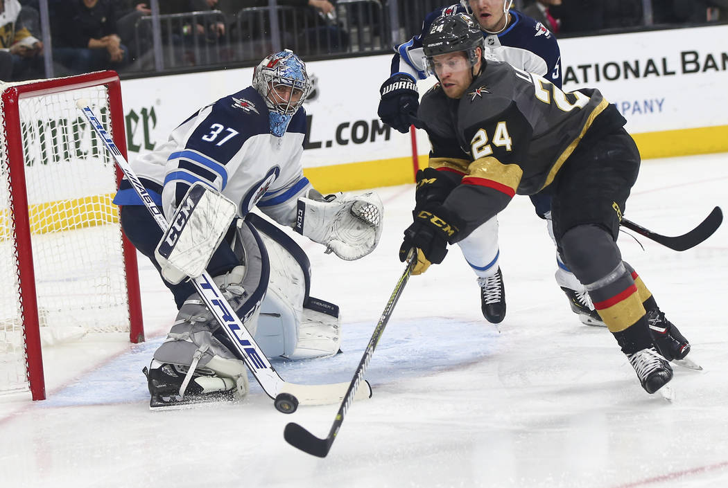 Golden Knights center Oscar Lindberg (24) tries to get the puck in past Winnipeg Jets goaltender Connor Hellebuyck (37) during the second period of an NHL hockey game at T-Mobile Arena in Las Vega ...