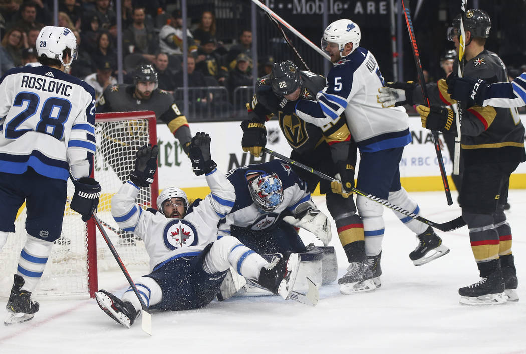 Winnipeg Jets left wing Mathieu Perreault, left, falls on the ice next to Winnipeg Jets goaltender Connor Hellebuyck (37) as Golden Knights defenseman Nick Holden (22) and Winnipeg Jets defenseman ...