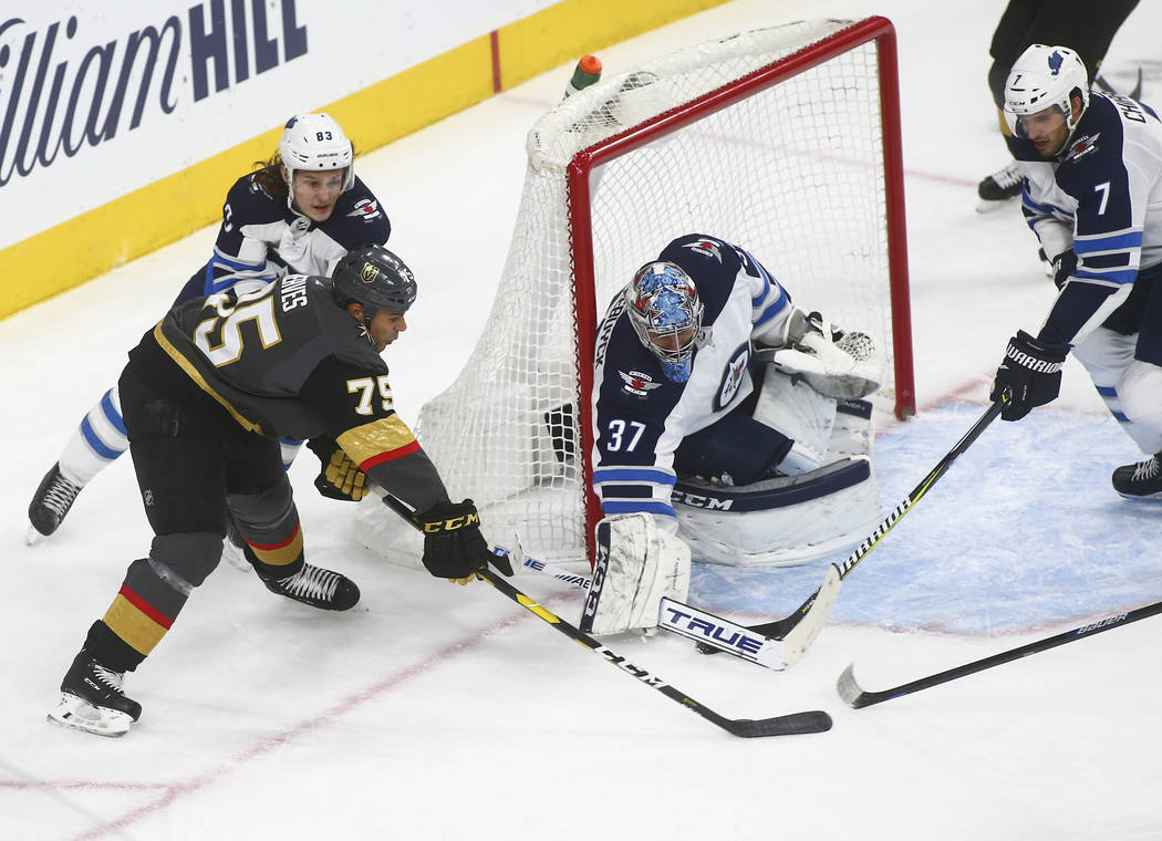 Golden Knights right wing Ryan Reaves (75) tries to get the puck in against Winnipeg Jets goaltender Connor Hellebuyck (37) during the third period of an NHL hockey game at T-Mobile Arena in Las V ...