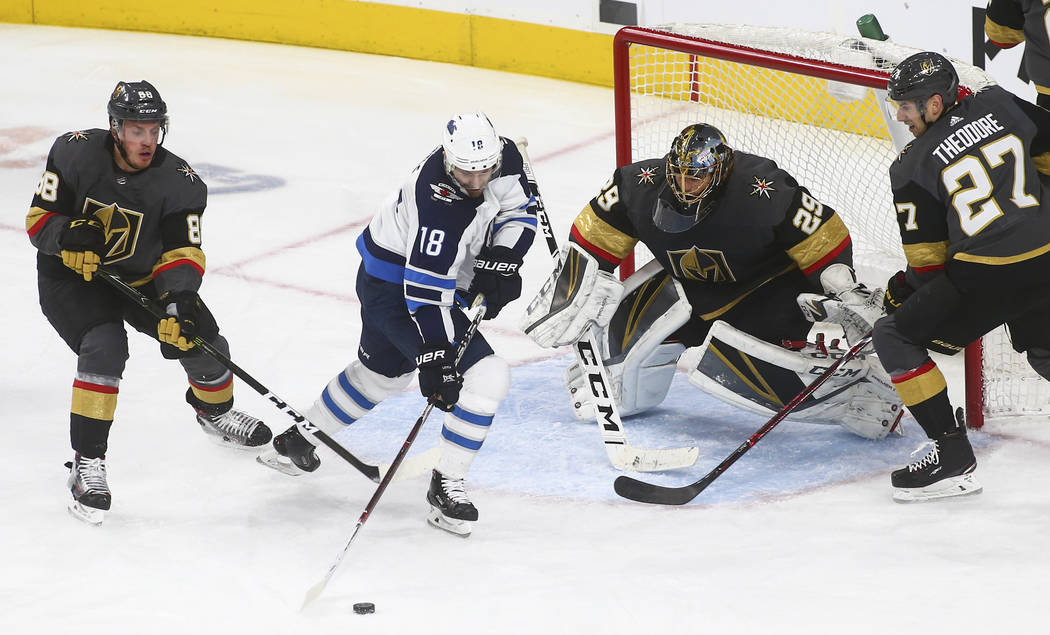 Winnipeg Jets center Bryan Little (18) tries to get the puck in against Golden Knights goaltender Marc-Andre Fleury (29) as Golden Knights defensemen Nate Schmidt (88) and Shea Theodore (27) defen ...