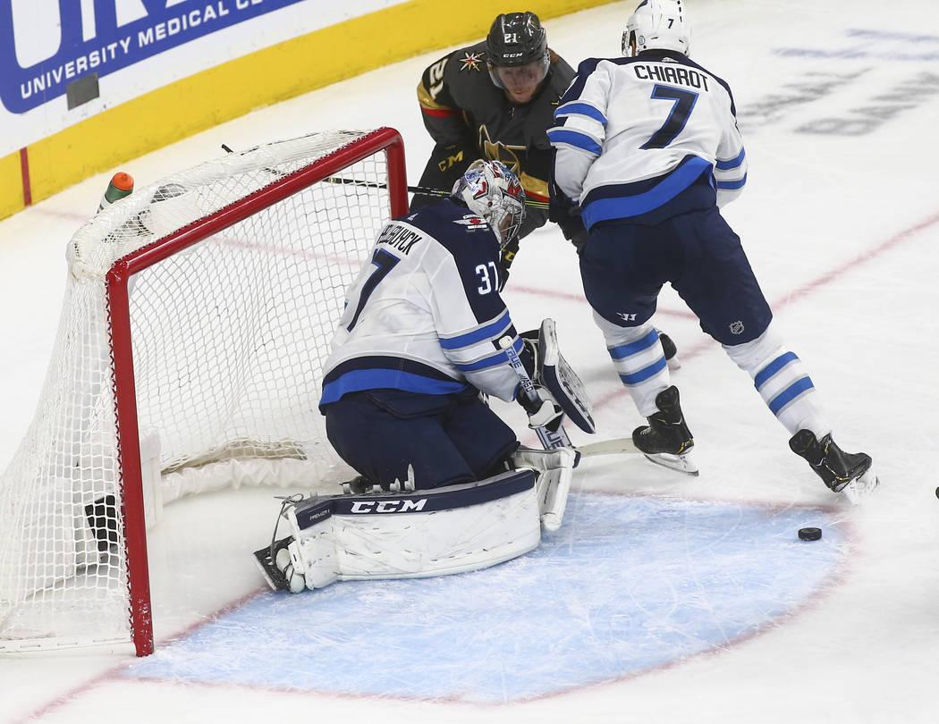 Golden Knights center Cody Eakin (21) tries to get to the puck under pressure from Winnipeg Jets defenseman Ben Chiarot (7) while Winnipeg Jets goaltender Connor Hellebuyck (37) defends during the ...
