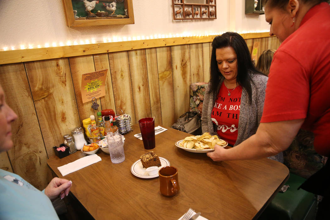 Server Joanne Lopez, right, serves food for customers Ranae Roquet, far left, and her friend Stacy Heath, visiting from Iowa, at the Omelet House in Las Vegas, Friday, Feb. 1, 2019. (Erik Verduzco ...