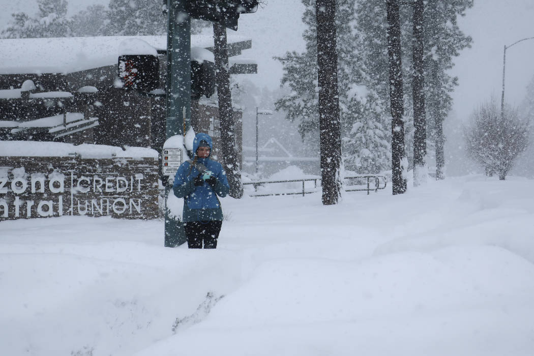 A pedestrian waits for a crossing signal in Flagstaff, Arizona, on Thursday, Feb. 21, 2019. Schools across northern Arizona canceled classes and some government offices decided to close amid a win ...