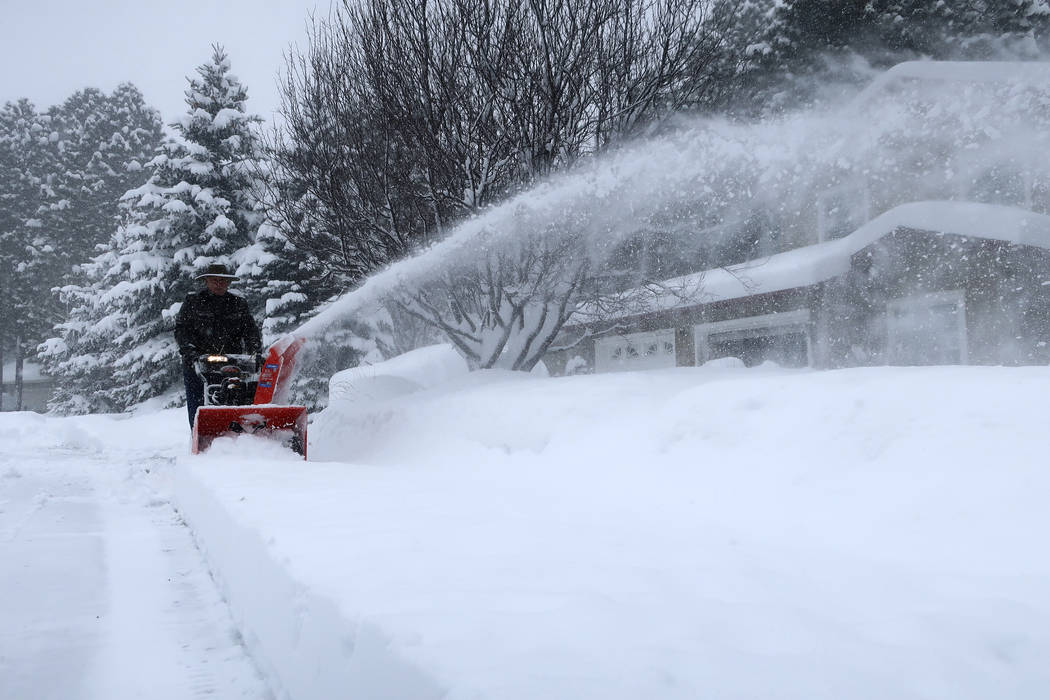 Richard Henn runs a snow blower down the sidewalk outside his home in Flagstaff, Arizona, on Thursday, Feb. 21, 2019. Schools across northern Arizona canceled classes and some government offices d ...