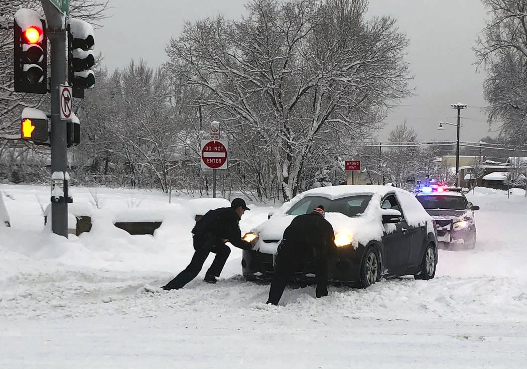 This photo provided by the Flagstaff, Ariz., Police Department shows a police officer, left, helping a motorist push a car stuck in snow in Flagstaff Friday morning, Feb. 22, 2019. Schools, public ...
