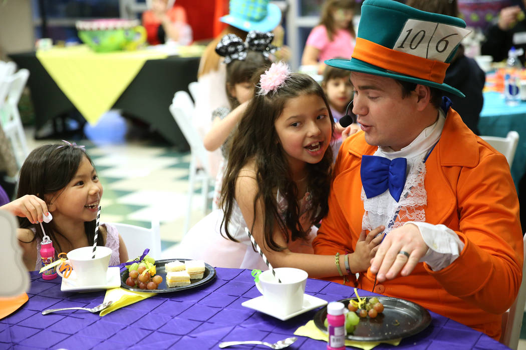 Lillian Roth, 6, from left, her friend Lola Torres, 6, talk to Dustin Winter, in costume as the Mad Hatter, during the annual Mad Hatter Tea Party for children and families at the Summerlin Counci ...