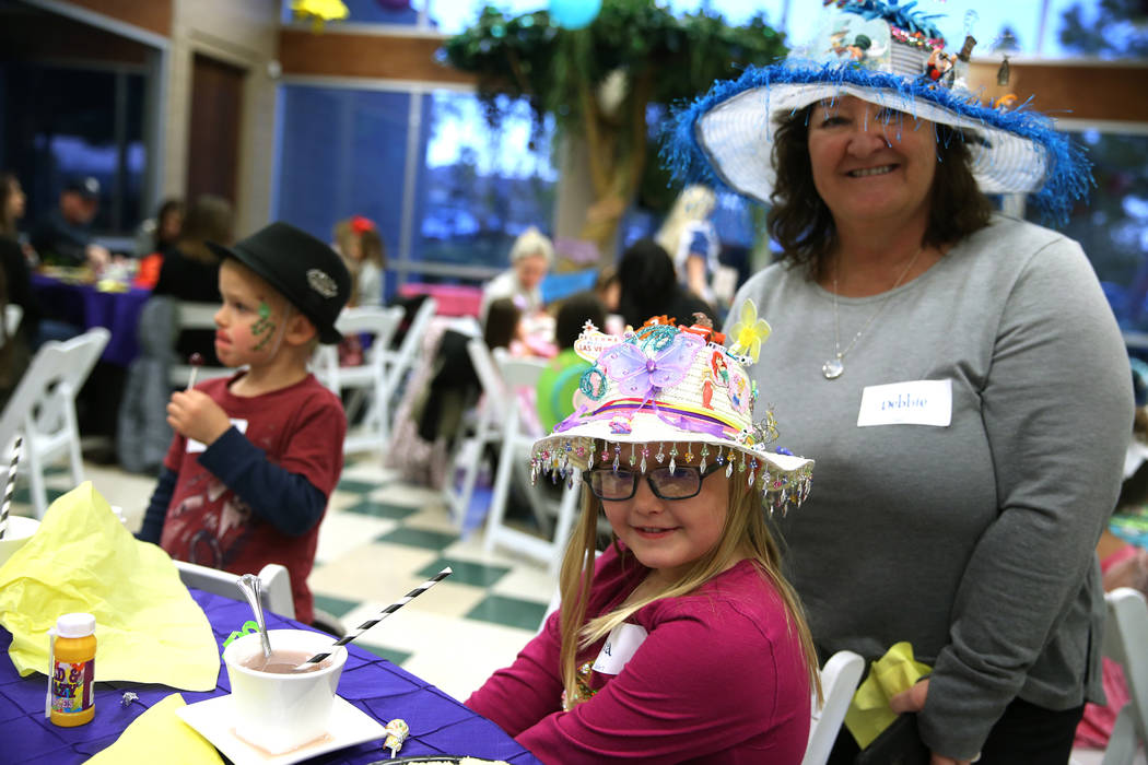 Gia Sauntman, 8, with her grandmother Debbie VanNatta, of Las Vegas, wear hats they made during the annual Mad Hatter Tea Party for children and families at the Summerlin Council in Las Vegas, Fri ...