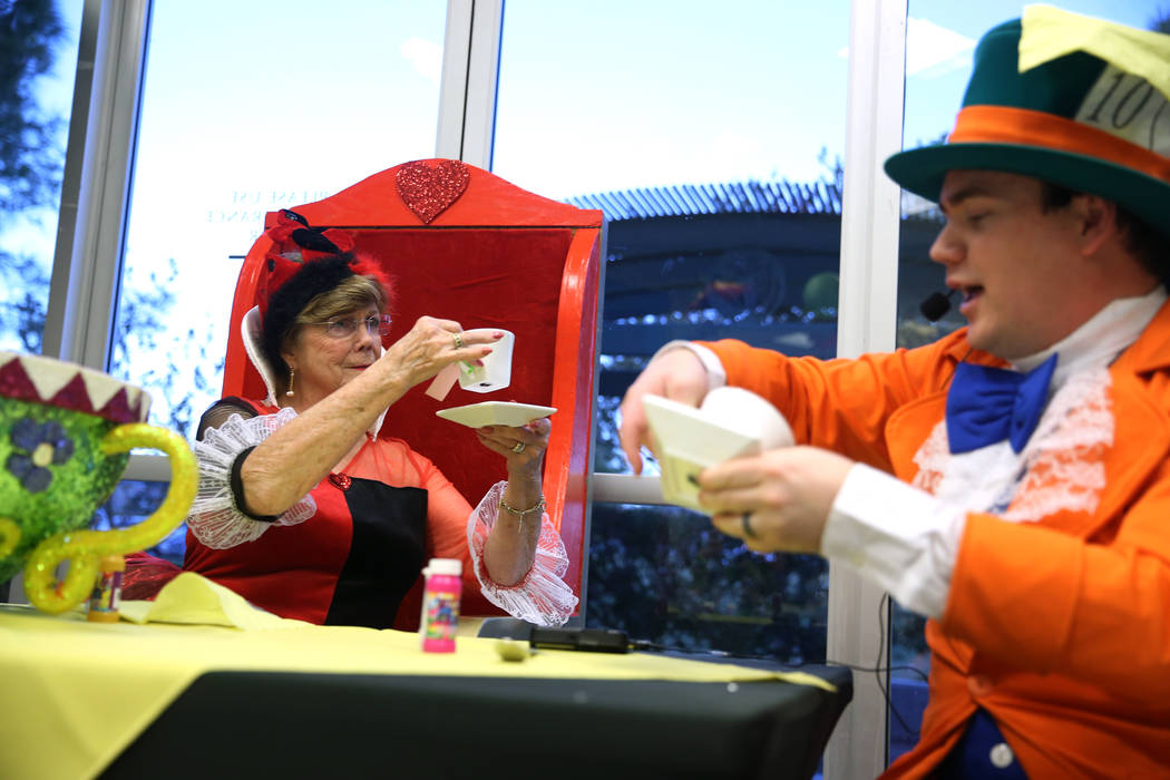 Gillian Kabat, left, in costume as the Queen of Hearts, and Dustin Winter, in costume as the Mad Hatter, entertain guests during the annual Mad Hatter Tea Party for children and families at the Su ...