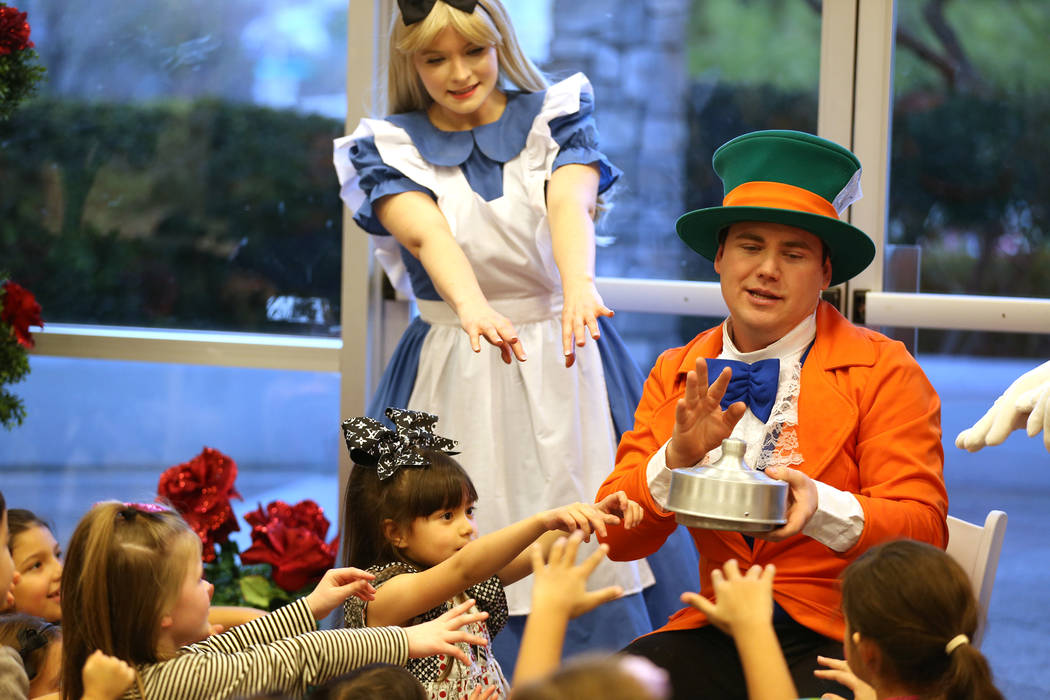 Brittney Reyes, left, in costume as Alice, and Dustin Winter, in costume as the Mad Hatter, perform a magic trick during the annual Mad Hatter Tea Party for children and families at the Summerlin ...
