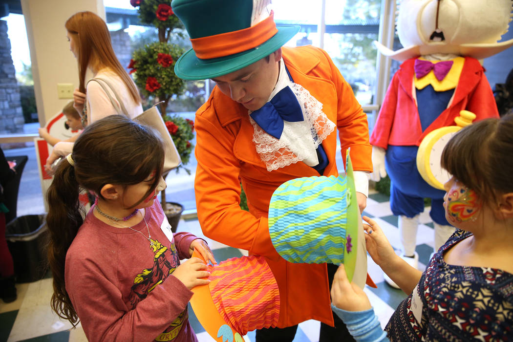 Dustin Winter, center, in costume as the Mad Hatter, talks to Yaara Osher, left, 7, and Morgan Kingsley, 7, during the annual Mad Hatter Tea Party for children and families at the Summerlin Counci ...