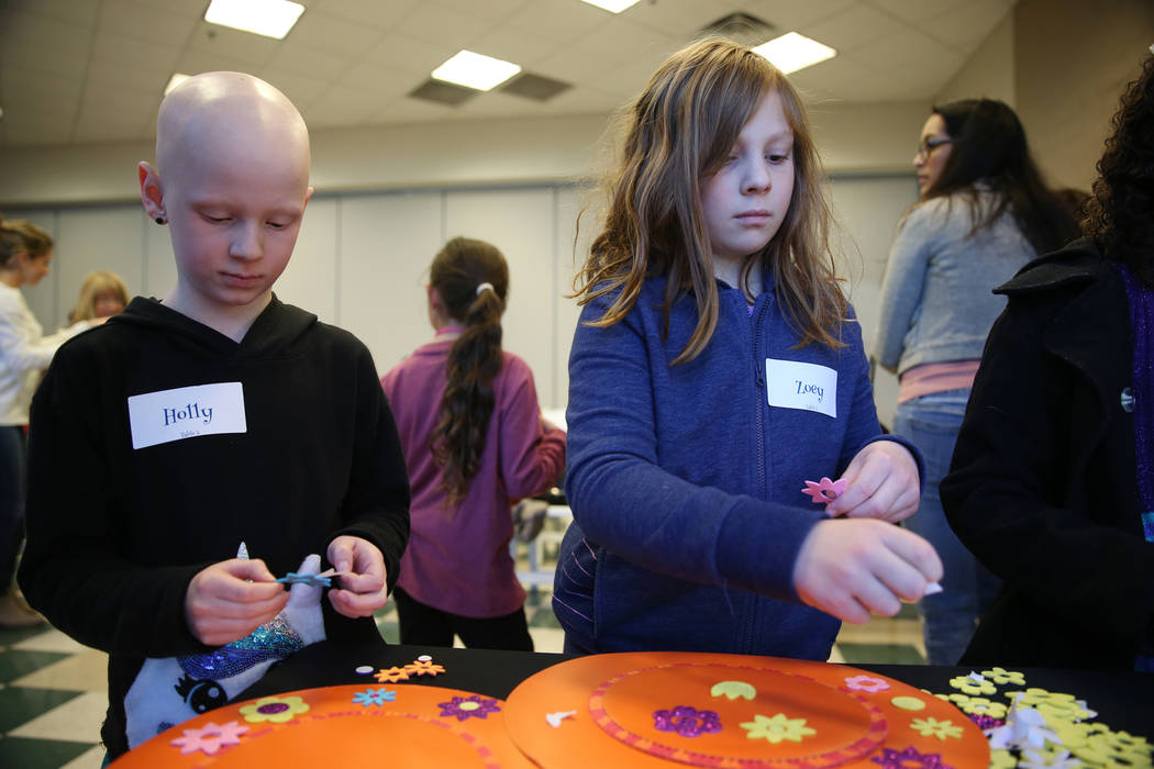 Holly Roger, left, 8, and her friend Zoey Kim, 8, make hats during the annual Mad Hatter Tea Party for children and families at the Summerlin Council in Las Vegas, Friday, Feb. 22, 2019. (Erik Ver ...