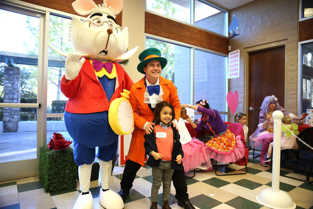 Oliver Ivanov, 5, of Las Vegas, is photographed with the White Rabbit and Dustin Winter, as the Mad Hatter, during the annual Mad Hatter Tea Party for children and families at the Summerlin Counci ...