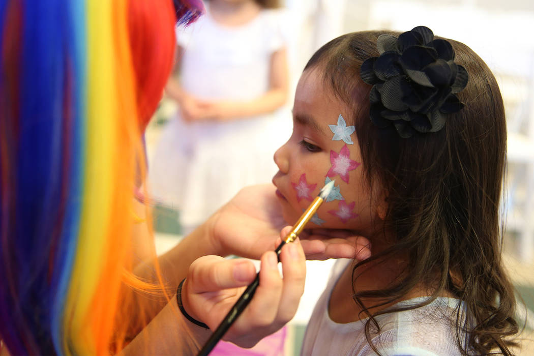 Haylee Isidro, 4, of Las Vegas, get a face painting during the annual Mad Hatter Tea Party for children and families at the Summerlin Council in Las Vegas, Friday, Feb. 22, 2019. (Erik Verduzco/La ...