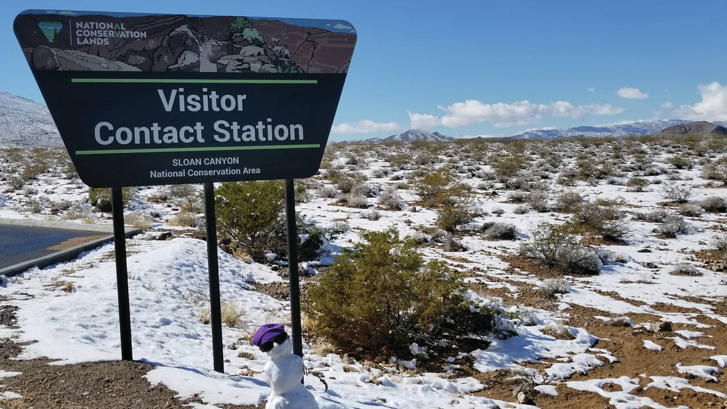 Hikers hitting the snowy trail leading from the Sloan Canyon Visitor Contact Station on Feb. 18. (Natalie Burt)