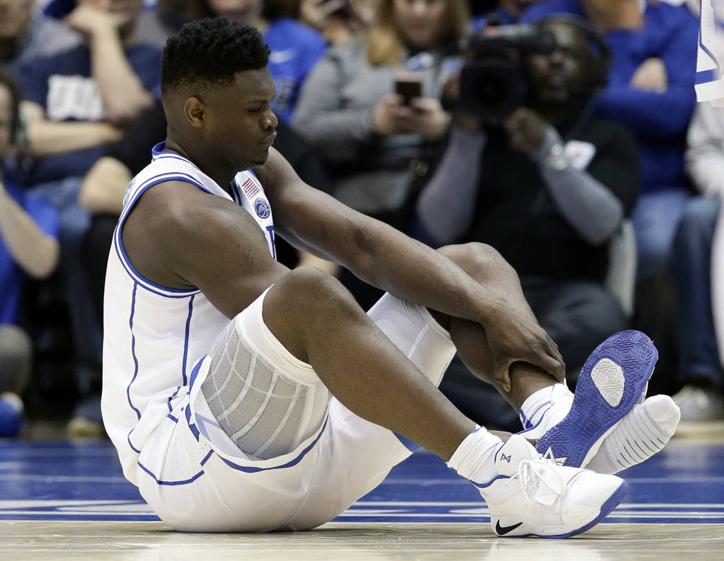 Duke's Zion Williamson sits on the floor following an injury during the first half of an NCAA college basketball game against North Carolina, in Durham, N.C., Wednesday, Feb. 20, 2019. Duke might ...