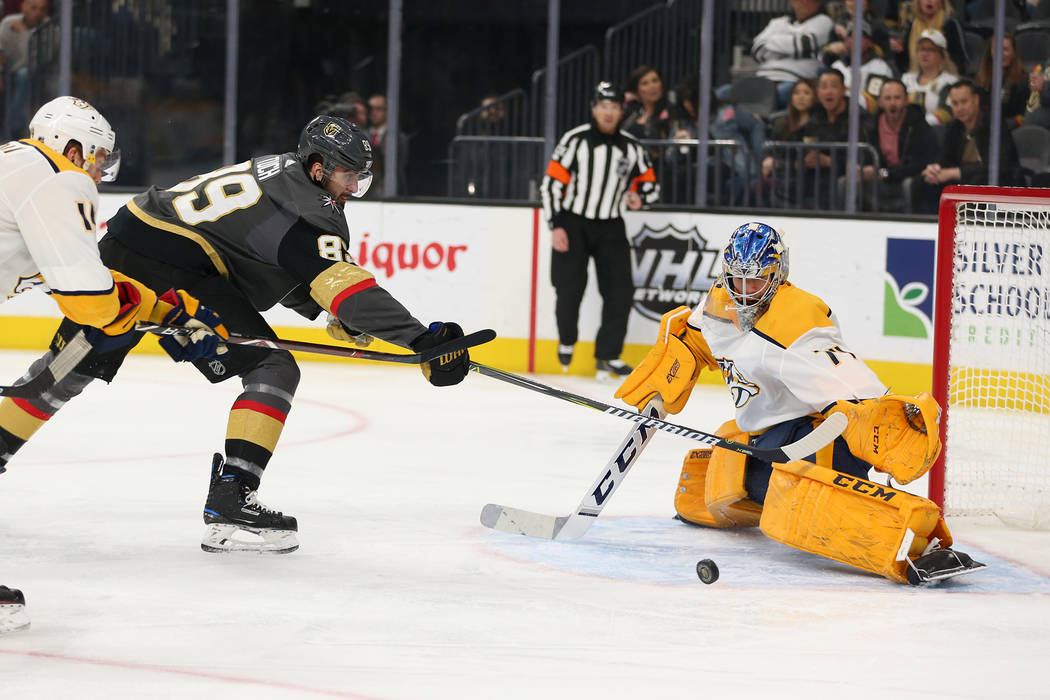 Vegas Golden Knights right wing Alex Tuch (89) reaches for the puck as Nashville Predators goaltender Juuse Saros (74) defends during the first period of an NHL hockey game at T-Mobile Arena in La ...