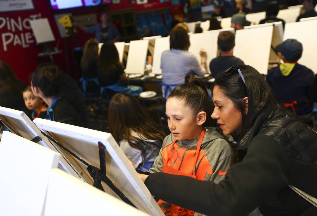 Rocio DeAngelis of Henderson, right, helps her daughter Abby, 7, during a painting session featuring a portrait of Golden Knights mascot Chance at Pinot's Palette at The District in Henderson on S ...