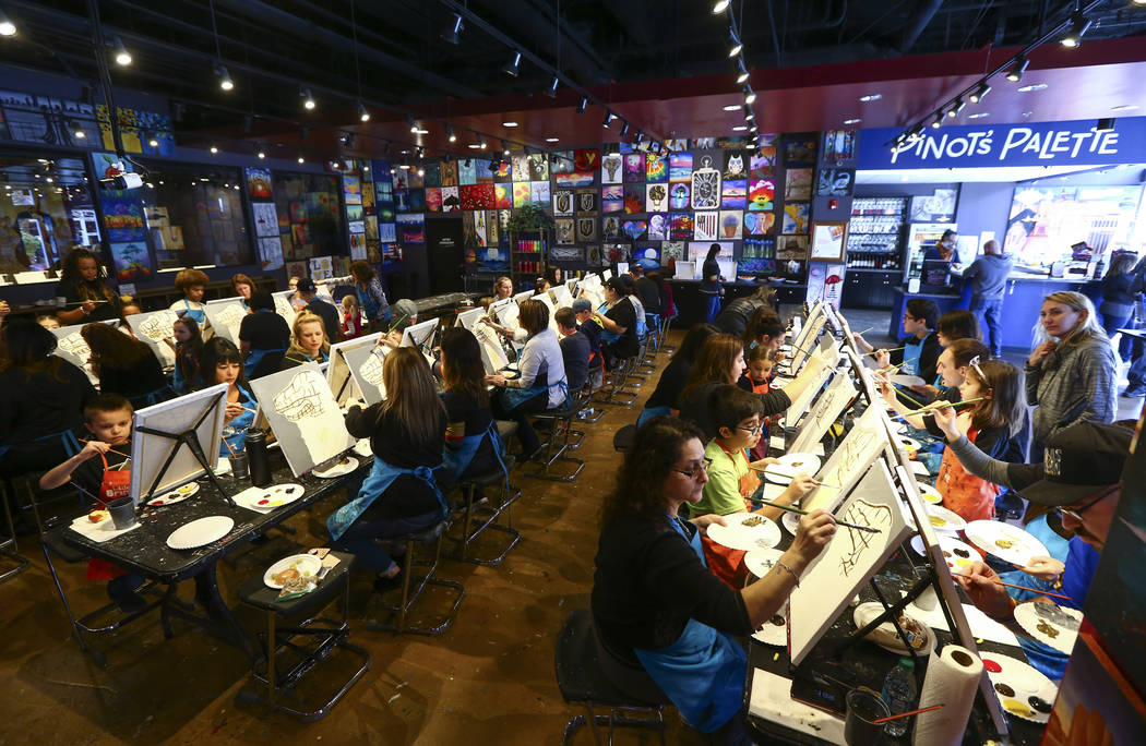 People paint during a painting session featuring a portrait of Golden Knights mascot Chance at Pinot's Palette at The District in Henderson on Sunday, Feb. 24, 2019. The event was held as a fundra ...