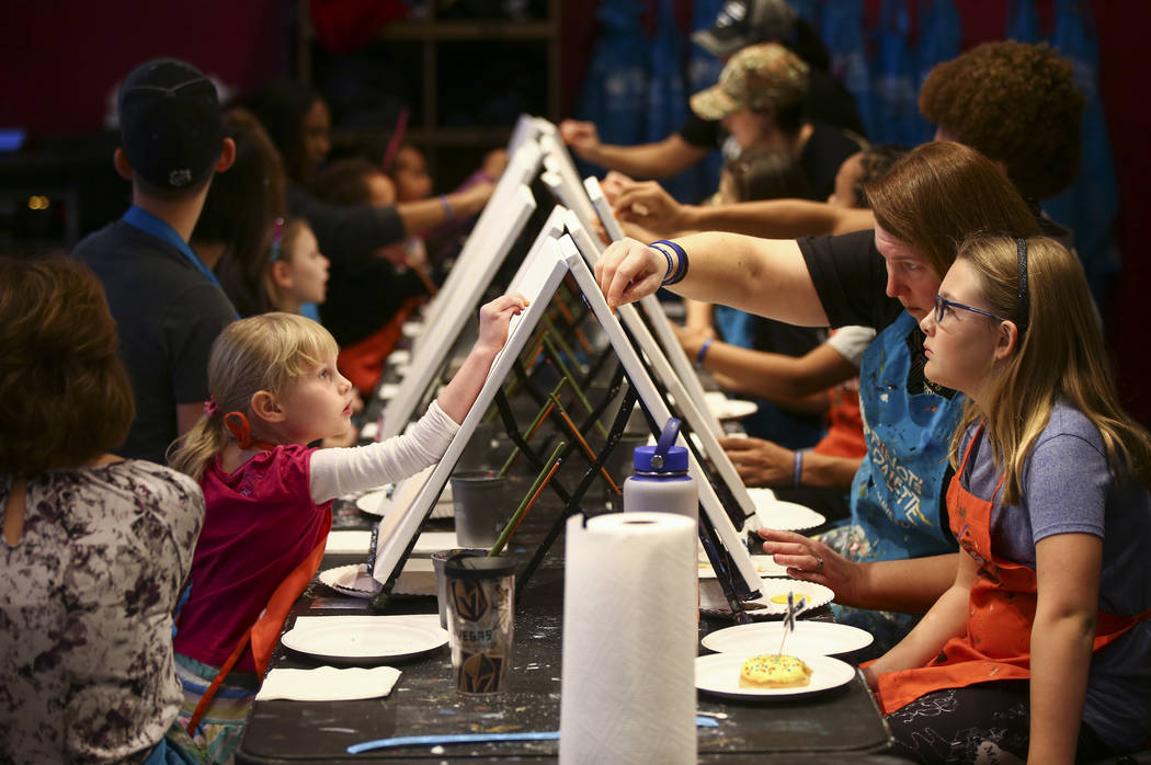 Aubree Clark, 5, left, paints across from Elizabeth Shea, center right, and her daughter Abby Shea, 9, during a painting session featuring a portrait of Golden Knights mascot Chance at Pinot's Pal ...