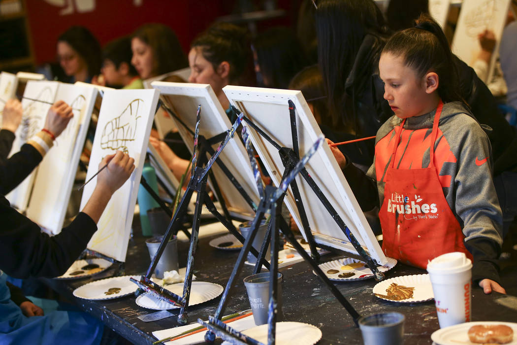 Abby DeAngelis, 7, paints during a painting session featuring a portrait of Golden Knights mascot Chance at Pinot's Palette at The District in Henderson on Sunday, Feb. 24, 2019. The event was hel ...