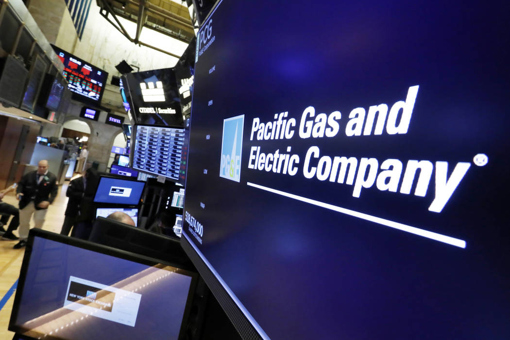 In this Jan. 14, 2019, file photo the logo for Pacific Gas & Electric Co. appears above a trading post on the floor of the New York Stock Exchange. (AP Photo/Richard Drew, File)
