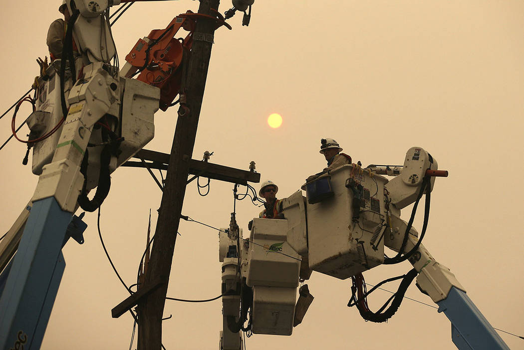 Pacific Gas & Electric crews work to restore power lines in Paradise, Calif., in November 2018. (AP Photo/Rich Pedroncelli)