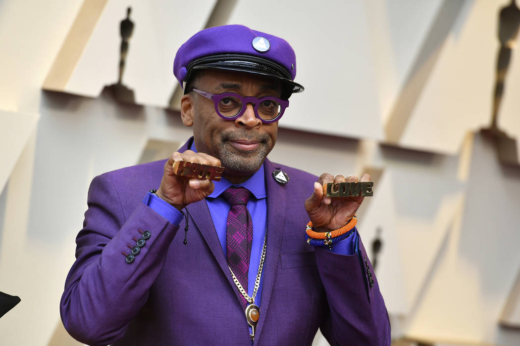 "Spike Lee holds up brass knuckles reading ""hate"" and ""love"" from his iconic film ""Do The Right Thing"" as he arrives at the Oscars on Sunday, Feb. 24, 2019, at the Dol ..."