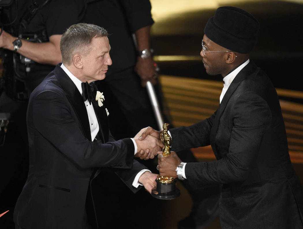 "Daniel Craig, left, presents Mahershala Ali with the award for best performance by an actor in a supporting role for ""Green Book"" at the Oscars on Sunday, Feb. 24, 2019, at the Dolby The ..."