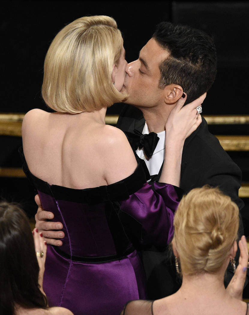"Lucy Boynton, left, kisses Rami Malek in the audience after he is announced winner of the award for best performance by an actor in a leading role for ""Bohemian Rhapsody"" at the Oscars o ..."