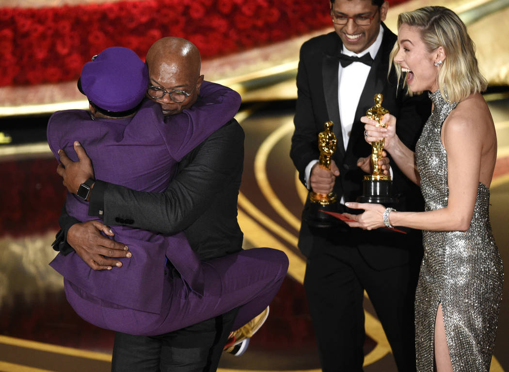 "Samuel L. Jackson, center left, embraces Spike Lee, winner of the award for best adapted screenplay for ""BlacKkKlansman"" as Brie Larson, right, looks on, at the Oscars on Sunday, Feb. 24 ..."