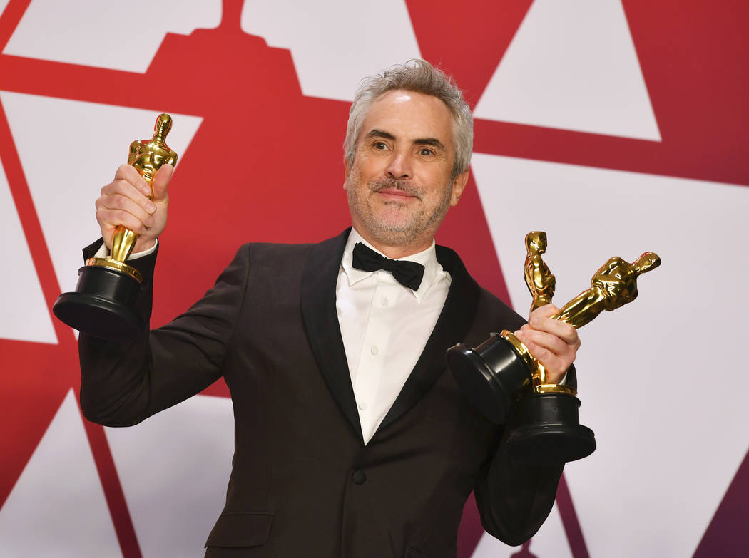 "Alfonso Cuaron poses with the awards for best director for ""Roma"", best foreign language film for ""Roma"", and best cinematography for ""Roma"" in the press room at the ..."