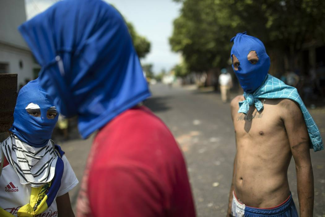 Masked anti-government protesters gather a few blocks from the border bridge in Urena, Venezuela, Sunday, Feb. 24, 2019, on the border with Colombia where Venezuelan soldiers continue to block hum ...