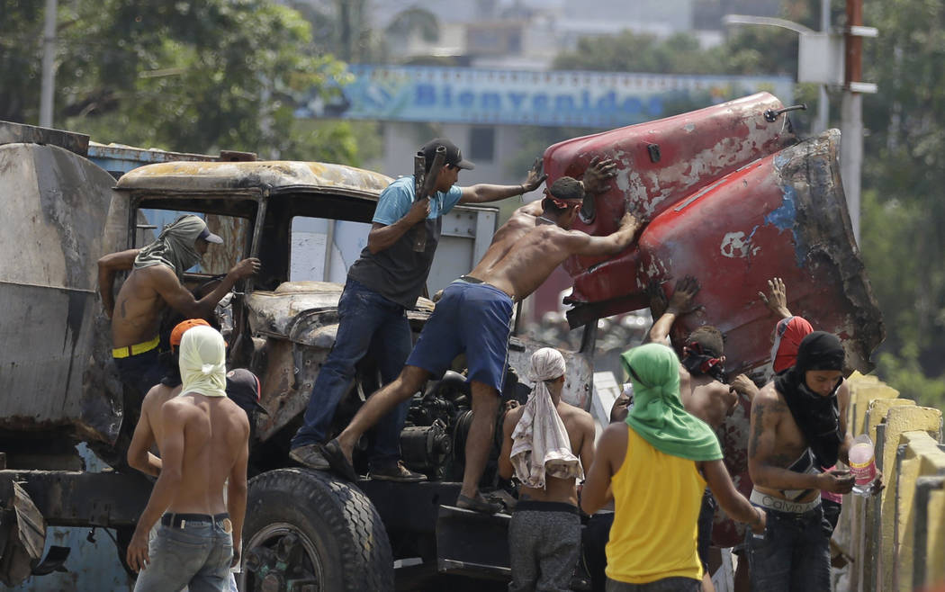 Venezuelans work to remove a roadblock created by Venezuelan National Guards on the Simon Bolivar International Bridge in La Parada, near Cucuta, Colombia, on the border with Venezuela, Sunday, Fe ...