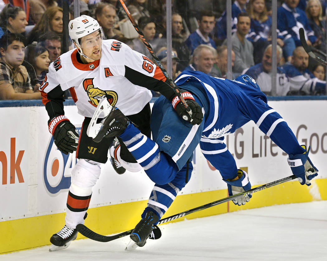 TORONTO, ON - OCTOBER 06: Ottawa Senators Right Wing Mark Stone (61) upends Toronto Maple Leafs Defenceman Ron Hainsey (2) during the regular season NHL game between the Ottawa Senators and the To ...