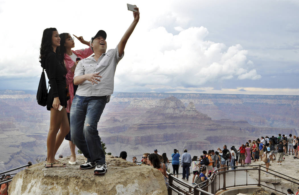 In this Aug. 2, 2015, file photo, tourists Joseph Lin, Ning Chao, center, and Linda Wang, left, pose for a selfie along the south rim at Grand Canyon National Park, Ariz. The Grand Canyon is celeb ...