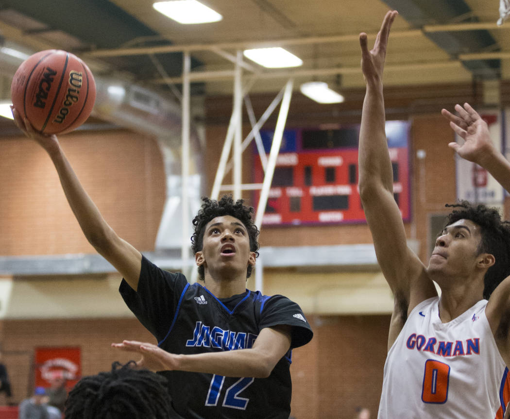 Desert Pines freshman Milos Uzan (12) splits Bishop Gorman junior forward Isaiah Cottrell (0) and sophomore guard Will McClendon (1) in the third quarter during the Southern Nevada boys basketball ...